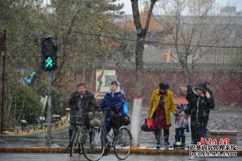 4月3日,民众在雪中步行过马路。当日,呼和浩特迎来降雪,气温骤然下降,不少民众纷纷加衣保暖。中新社记者 刘文华 摄