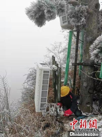 技术人员将数套每台约100斤的AAU设备(5G天线)人工搬运至金顶 王政 摄